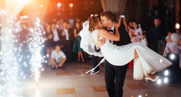 A bride and groom kiss in front of their guests at a wedding reception